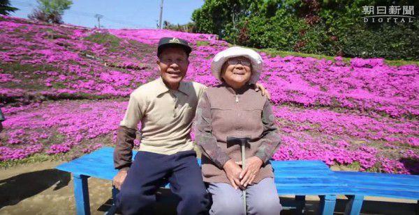 Stariji kineski par sjedi na klupi okruzebni mirisnim cvijecem