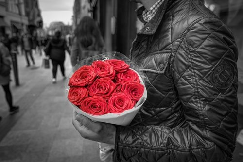 Momak sa buketom crvenih ruza